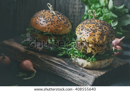 Two Homemade burgers with beef, fried onion and pea sprouts, served on wooden chopping board over wooden background. Dark rustic style. Natural day light with retro filter effect - stock photo