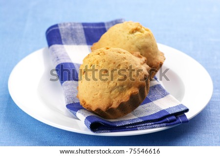 Two homemade cupcakes with checked napkin in white plate on blue tablecloth.