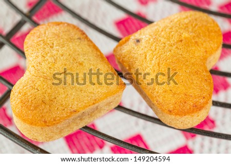 Two Homemade heart shaped banana muffins cooling on metal rack - stock photo