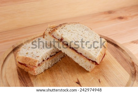 Two homemade peanut butter and jelly sandwiches on a wooden cutting board - stock photo