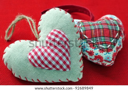 Two homemade sewn hearts on red background - stock photo