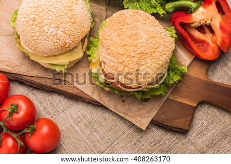 Two homemade vegetarian burgers with fresh organic vegetables on rustic wooden background. Top view with copy space. - stock photo