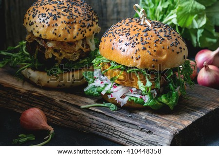 Two Homemade veggie burgers with sweet potato, fresh radish and pea sprouts, served on wooden chopping board over wooden background. Dark rustic style. Natural day light. - stock photo