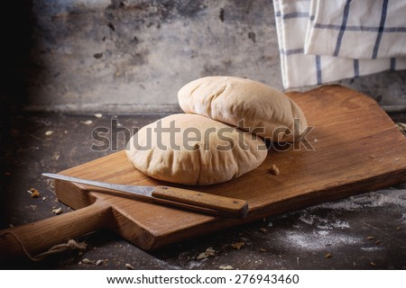Two homemade wholegrain pita bread on wooden cutting board, served with knife and flour over dark table. - stock photo