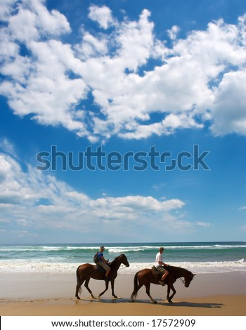 Two horse riders on beach.