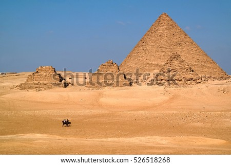 Two horse riders on the Giza Plateau pass by the Pyramids, Egypt