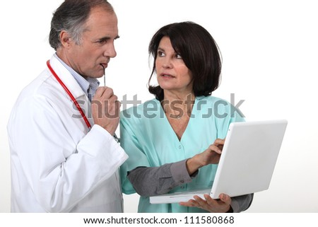 Two hospital workers with laptop - stock photo