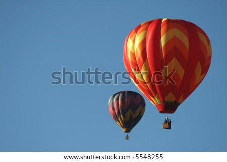 Two hot air balloons during early morning ascend. - stock photo