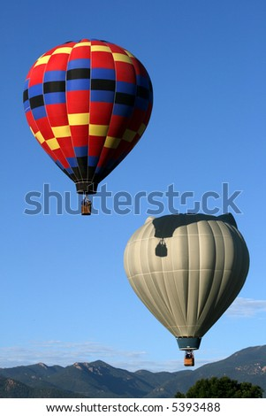 Two hot air balloons early morning with peaks of the Rocky Mountains - stock photo