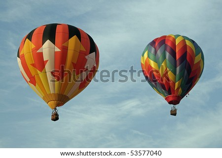 two hot air balloons floating against a cloud streaked blue sky