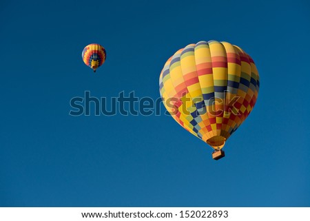 Two hot air balloons just after lift off.  Set against a deep blue sky.