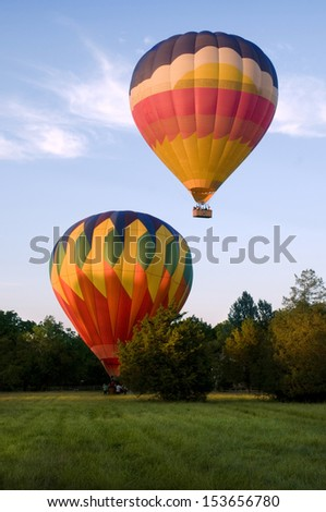Two hot-air balloons taking off or landing in a field. One is on the ground. The other is airborne. - stock photo