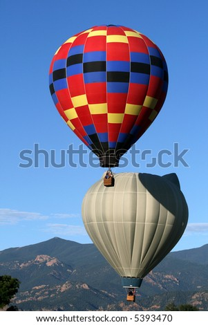 Two hot air balloons with the Rocky Mountains as backdrop - early morning - stock photo