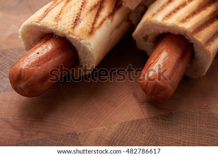 Two hot dogs lying on the wooden table
