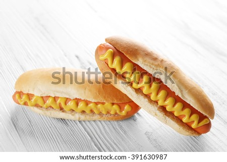 Two hot dogs on wooden background