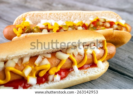 Two hot dogs with ketchup  closeup  , yellow mustard and onion on gray wooden surface