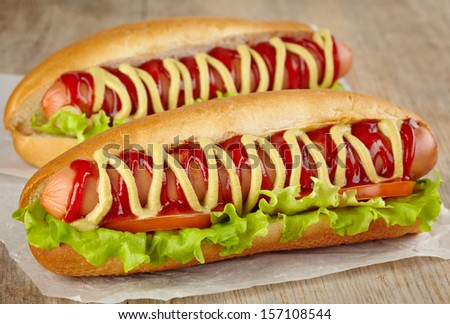 Two hot dogs with lettuce and tomato - stock photo