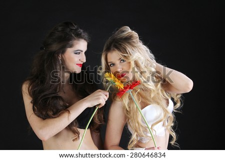 Two hot sexy female in lingerie with flowers on black background - stock photo