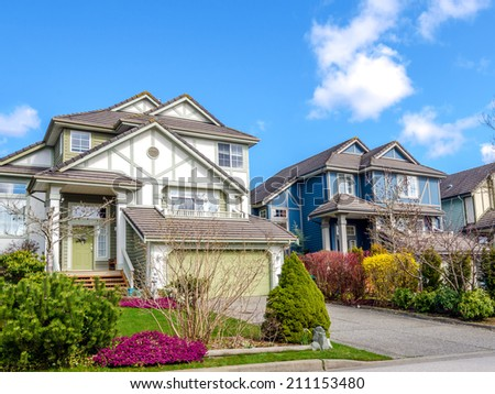 Two houses with beautiful landscaping on a sunny street. - stock photo