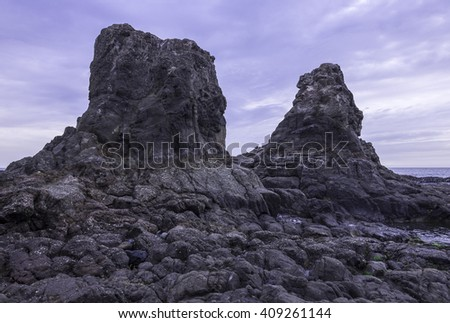 Two huge rocks tower above the sea at low tide on rocky coastline of Rosarito, Baja California, Mexico under moody cloudy grey sky - stock photo