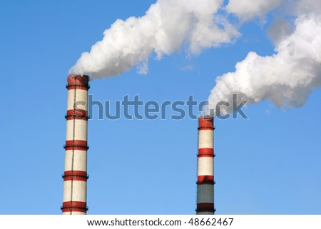 Two huge steaming plant power plant tubes over blue sky