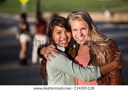 Two hugging female students hugging each other outdoors - stock photo