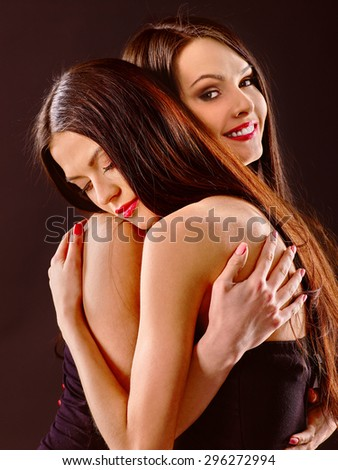 Two hugging lesbian women kissing .Grey background. - stock photo