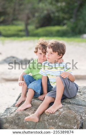 Two hugging little brothers sitting on the beach