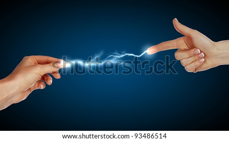 Two human hands in contact with bright flash - stock photo