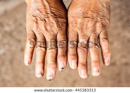 Two human hands on cement background.