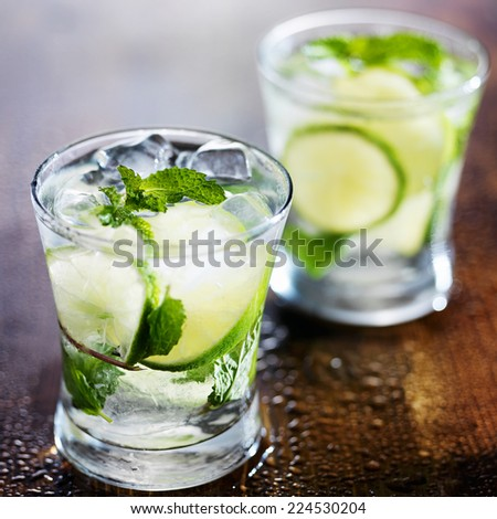 two ice cold fresh mojito cocktails on wooden table - stock photo