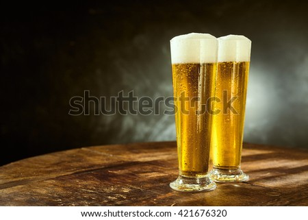 Two ice cold frothy beers in elegant long glasses standing on an old rustic wooden table in a pub, bar or tavern with copy space on a slate background - stock photo