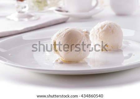 two ice cream scoops on white plate close-up against decorated table  - stock photo