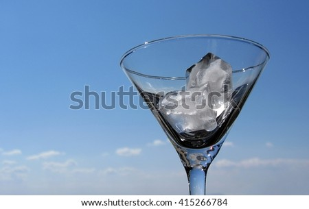 Two ice cubes in Martini cocktail glass against the blue sky.