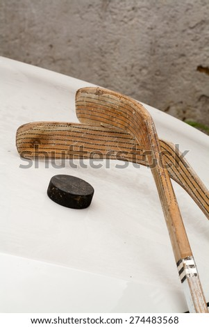 two ice hockey sticks with vintage old hockey puck on white background, Ice Hockey World Championships, used implements, natural and real photo - stock photo