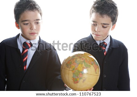 Two identical twin brothers holding a globe map while standing by a window and wearing their school uniform.