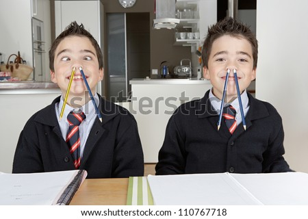 Two identical twin brothers playing with pencils while doing their homework at home on the kitchen table.