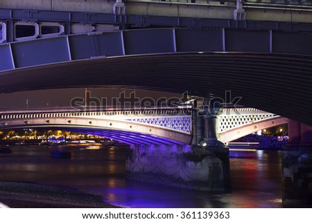 Two illuminated bridges over the River Thames at night with boats passing in background