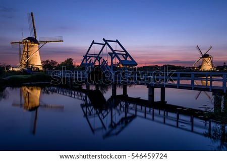 Two illuminated windmills and a drawbridge with reflection in the water of the canal in the last light at sunset in Kinderdijk in the Netherlands.