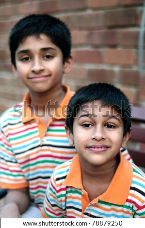 Two Indian brothers sitting happily at a local park - stock photo