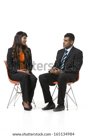 Two Indian Business People sitting down having a meeting. Indian man and woman business partners. isolated on a white background. - stock photo