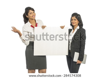 Two Indian business women with white board on white background. - stock photo