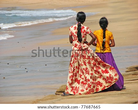Two Indian girls standing on the beach - stock photo