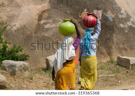 Two Indian women carry water on their heads in traditional pots  - stock photo
