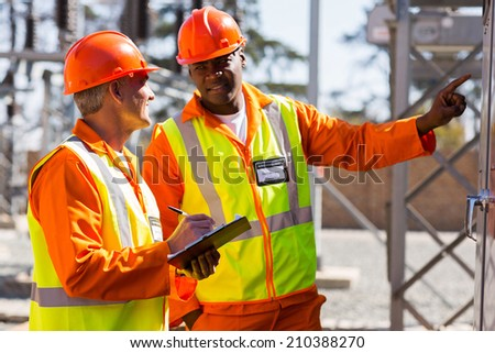 two industrial electricians taking machine readings at power plant