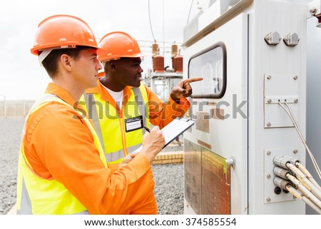 two industrial electricians taking machine readings at power plant - stock photo
