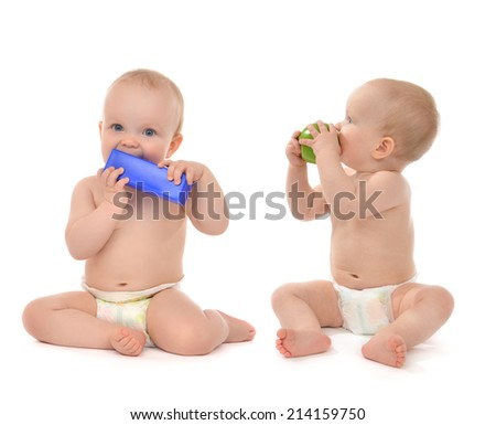 Two infant child baby toddlers sitting and eating blue toy brick and green apple in hand isolated on a white background - stock photo