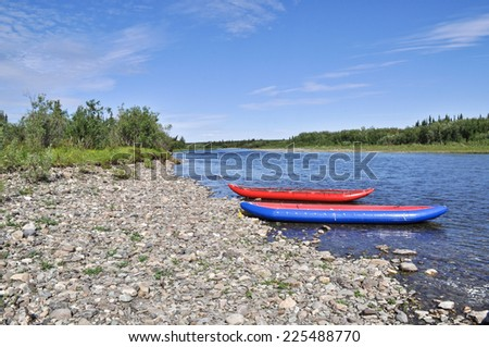 Two inflatable canoes on the shore of the North river. Polar Ural, Komi Republic, Russia. - stock photo