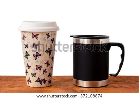 Two insulated coffee mugs on a wooden table. - stock photo