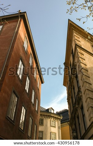 Two irregularly shaped house in the center of Stockholm in the autumn against the sky.
